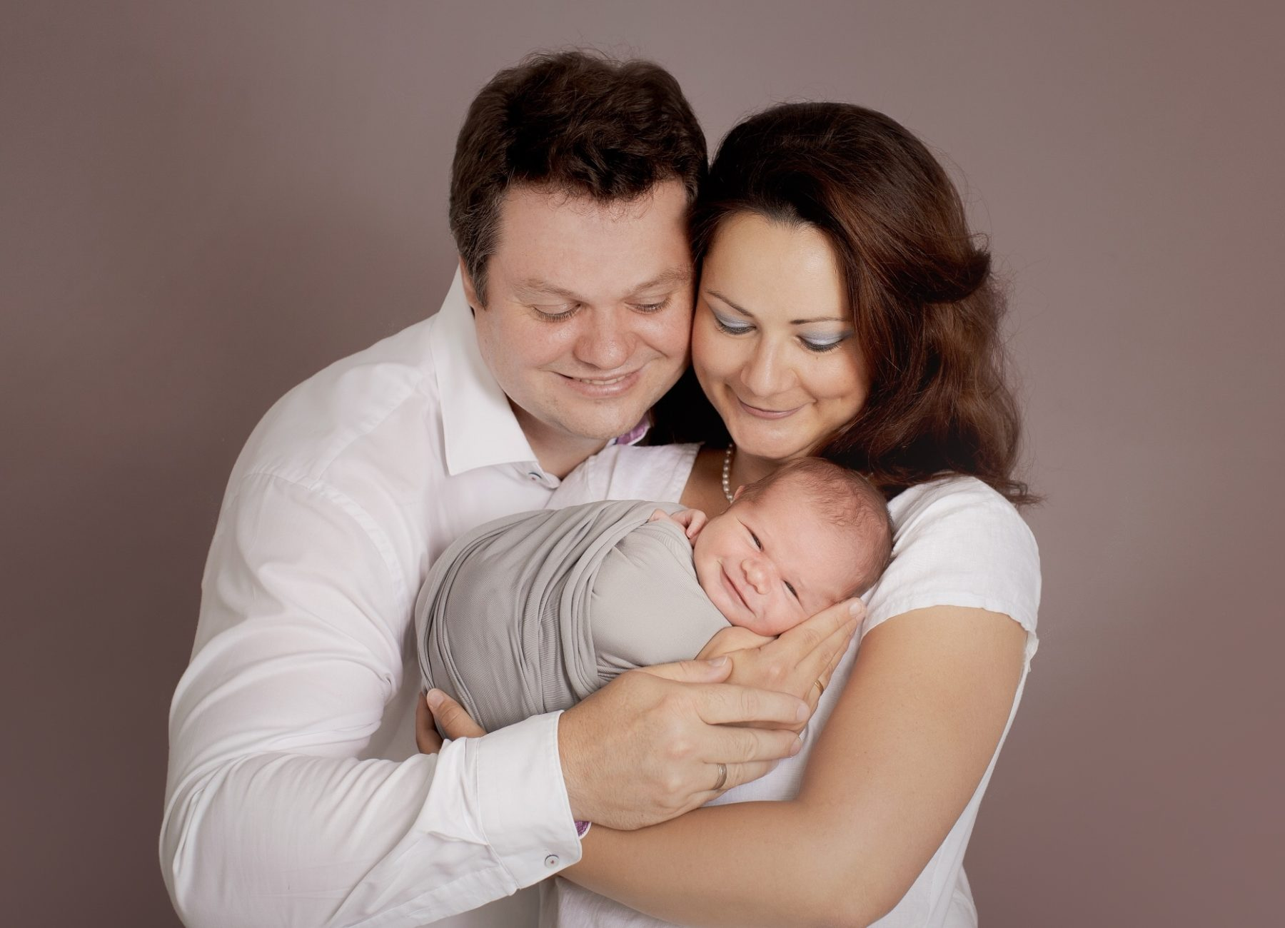 Eltern halten ein lächelndes Baby